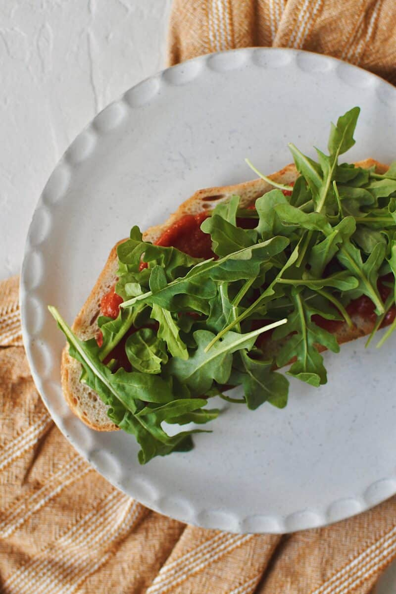 Building a Parmesan Chicken Sandwich, toasted bread with marinara sauce on top, a layer of arugula added.