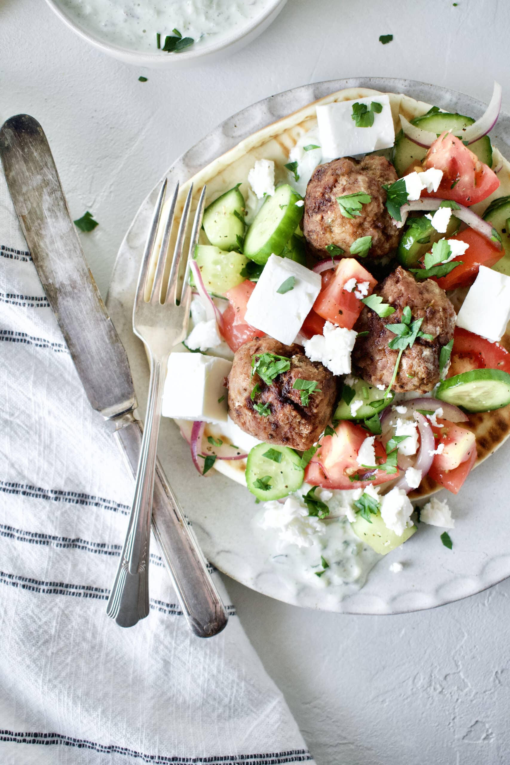 Greek Meatballs served with Greek Salad on top, over a pita bread with Tzatziki sauce.