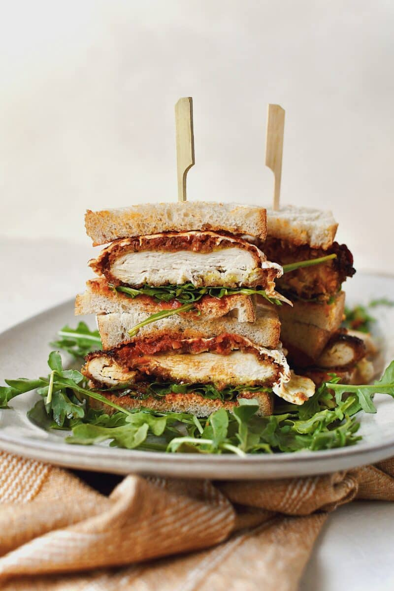 Parmesan Chicken Sandwich, sliced and stacked, on a platter on a bed of arugula.