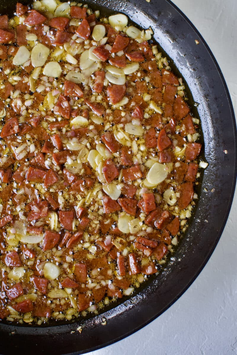 Onion, garlic, and chorizo cooking in olive oil.