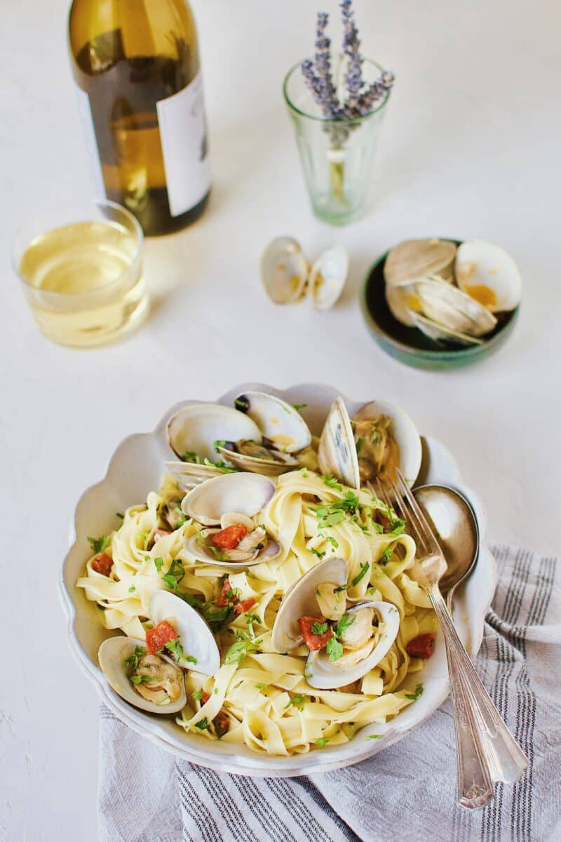 Linguine with Clam Sauce served in a bowl with a glass of white wine in the background.