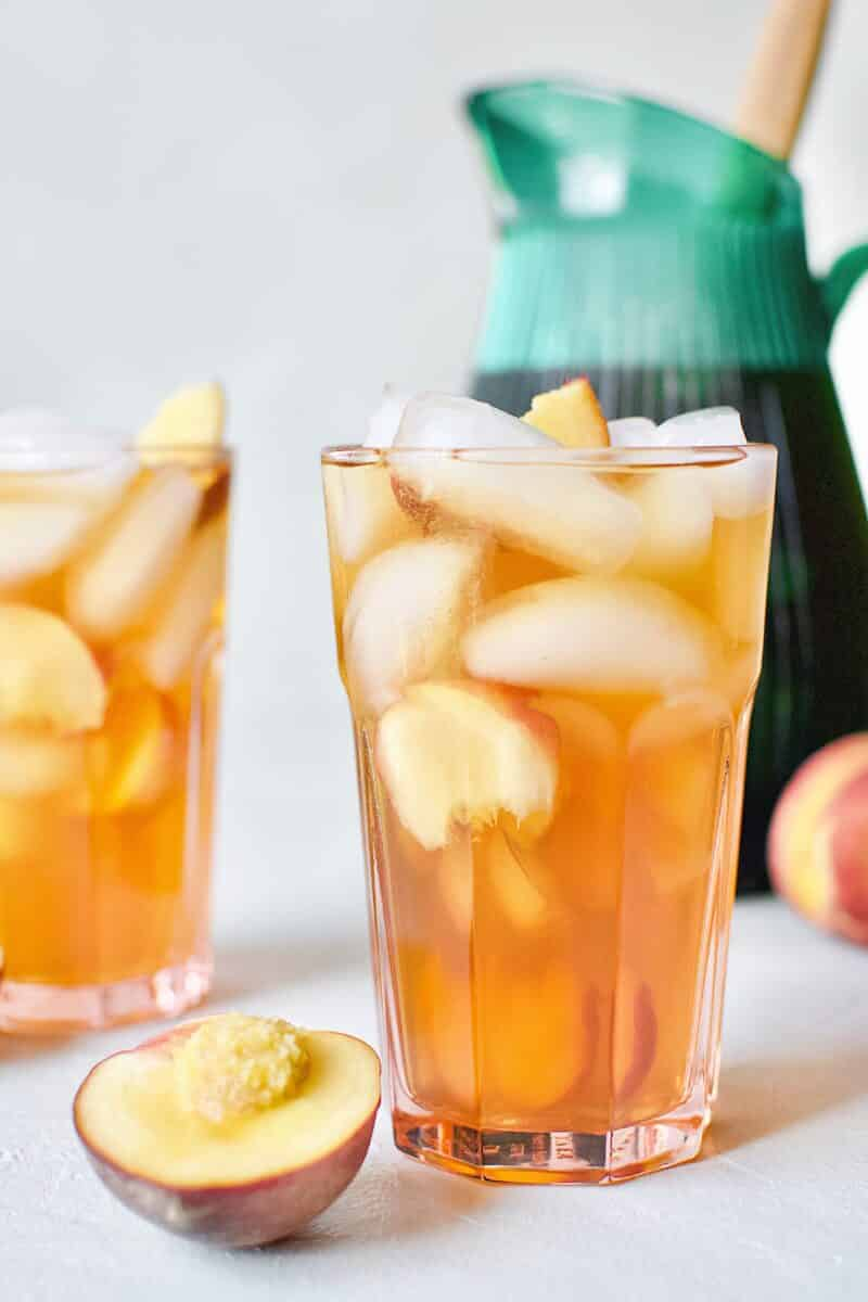 Peach Sangria in an ice filled glass with peach wedges.