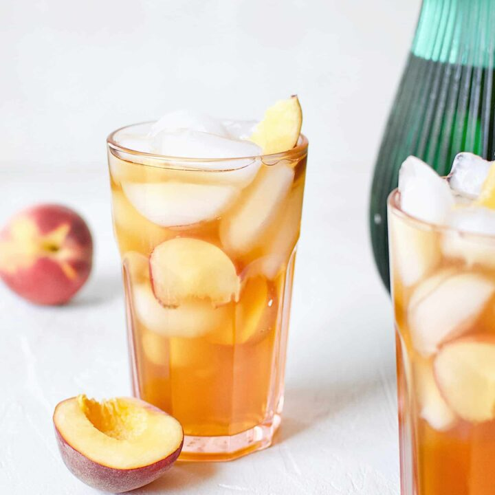 Peach Sangria in an ice-filled glass with peach wedges.