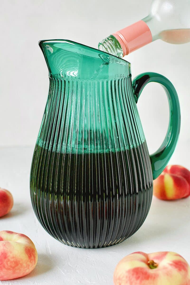 Adding the wine to a pitcher that already has the cooled peach sweet tea in it.