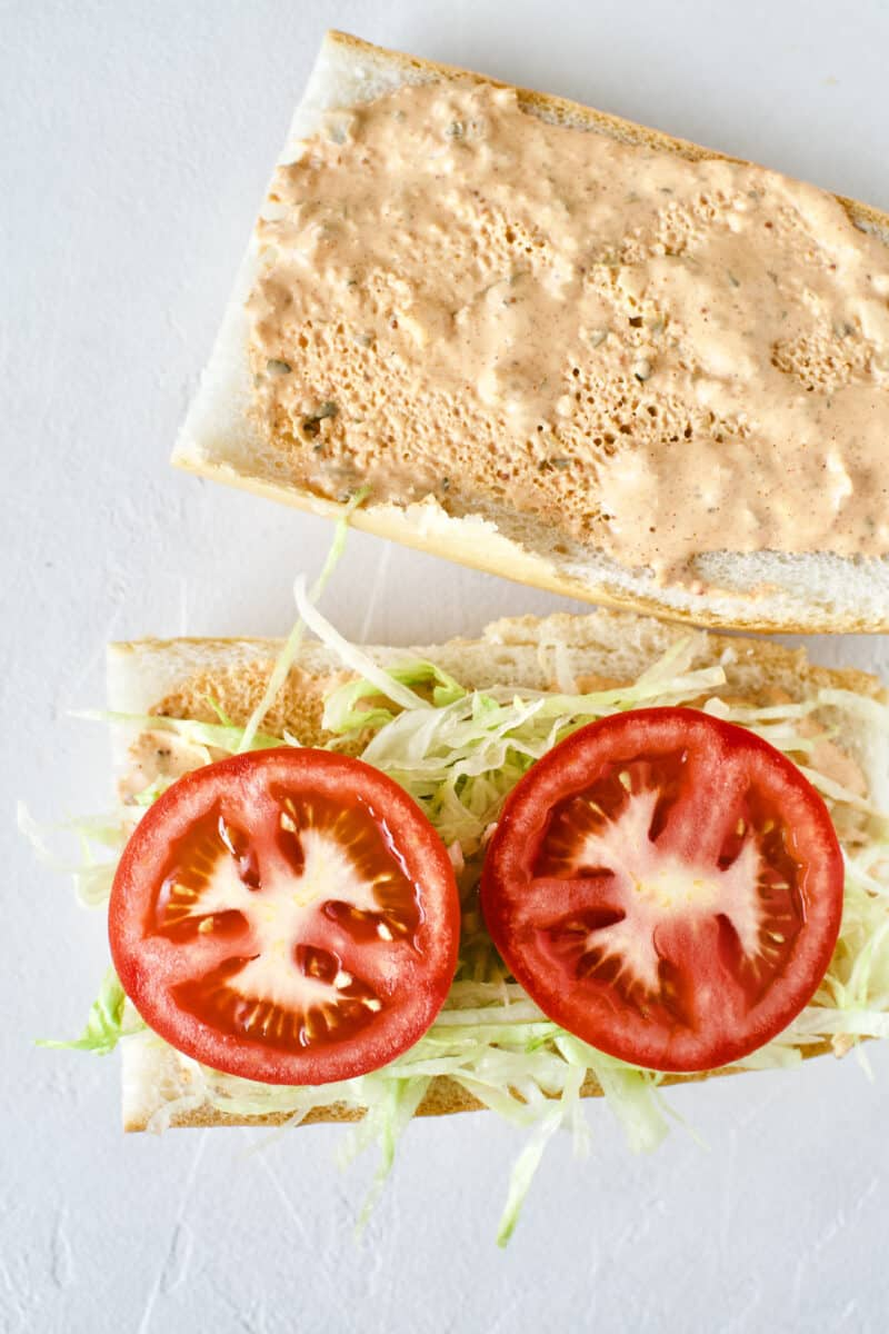 Building a Shrimp Po'boy Sandwich, french bread with homemade remoulade on both sides of the bread, shredded lettuce and tomato slices added.
