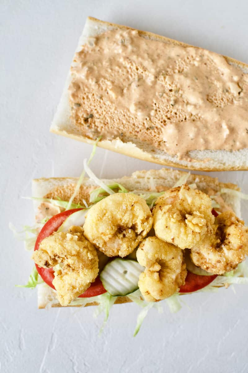 Building a Shrimp Po'boy Sandwich, french bread with homemade remoulade on both sides of the bread, shredded lettuce, tomato, and pickle slices added. Topped with freshly fried shrimp.
