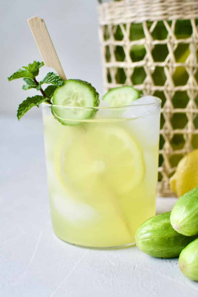 Cucumber Mint Lemonade in a glass with a skewer of lemon and cucumber slices and a sprig of mint.