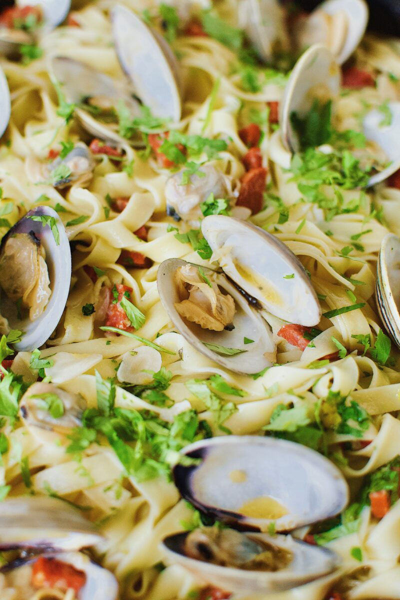 Pasta tossed with all ingredients, and served with clams added on top.