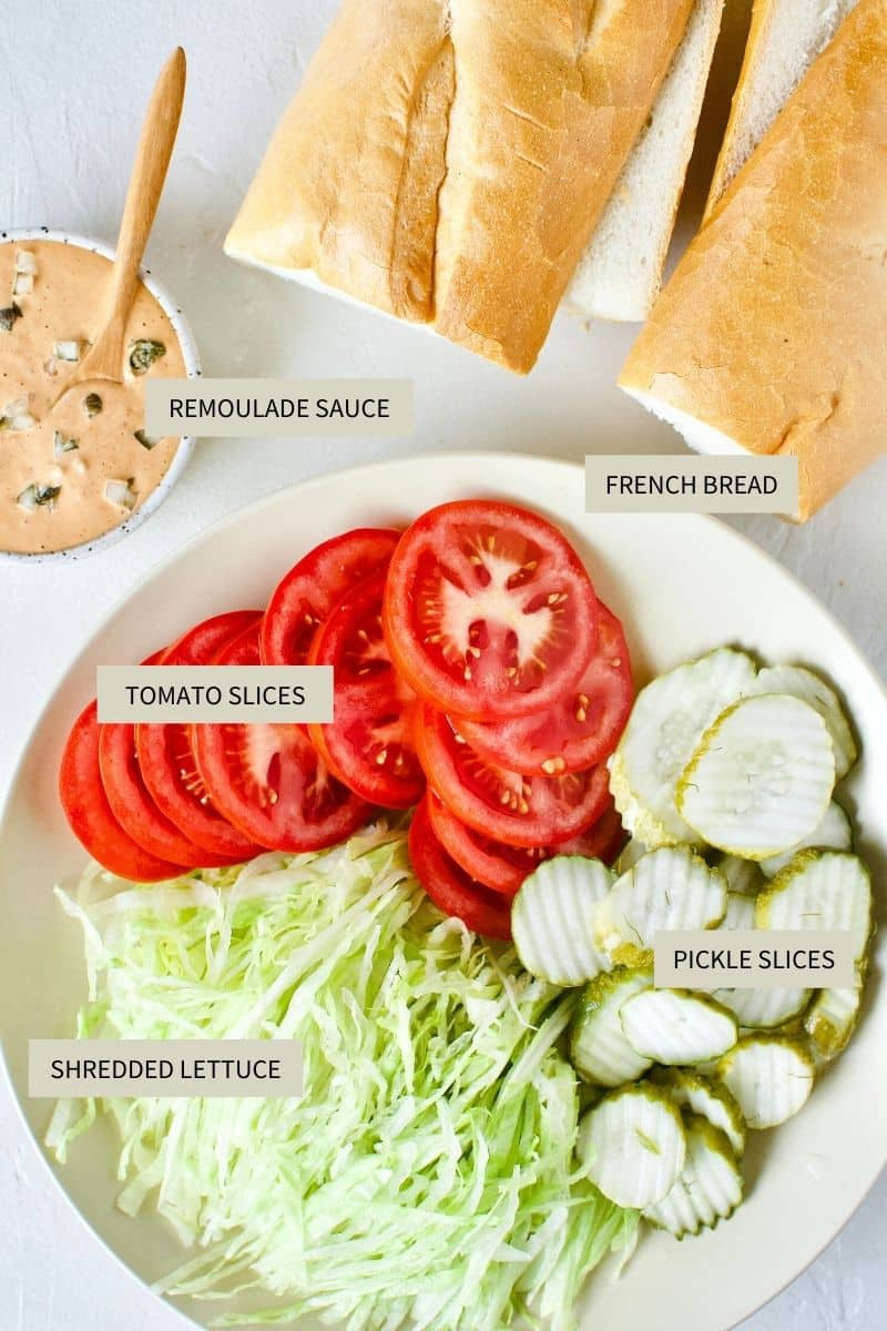 French Bread, remoulade, lettuce, tomato, and pickle slices for building Po'boy sandwiches.