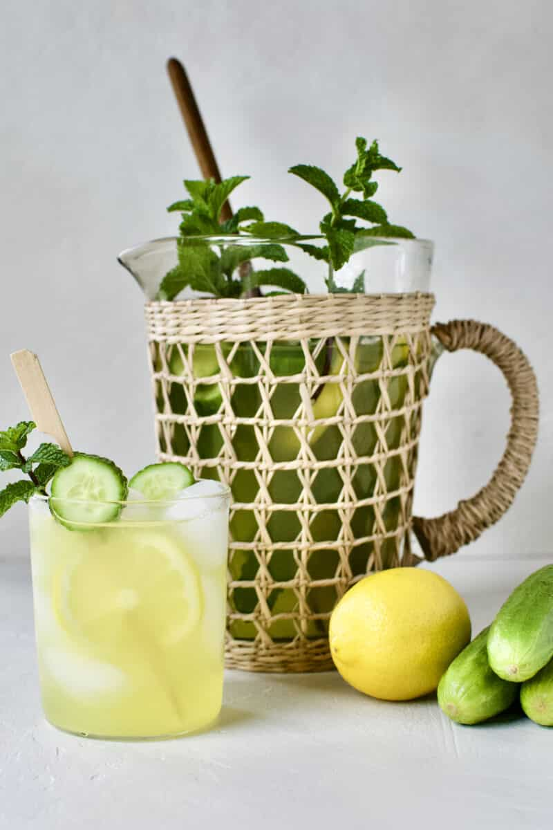 Cucumber Mint Lemonade in a glass with a skewer of lemon and cucumber slices and a sprig of mint. A pitcher of lemonade behind the glass.