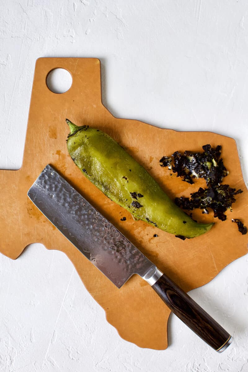 Cleaning a hatch chile by removing the charred skin with the back of a knife.