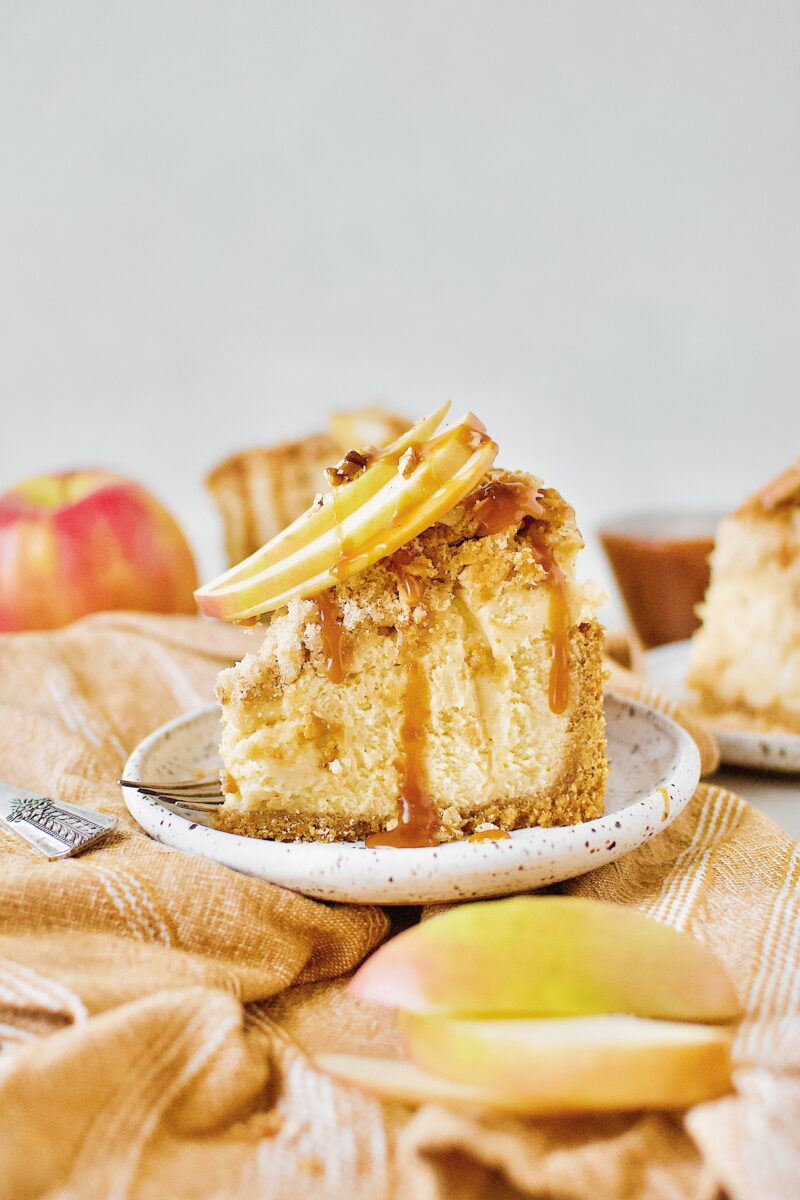 Caramel Apple Crisp Cheesecake topped with caramel sauce and sliced apples.