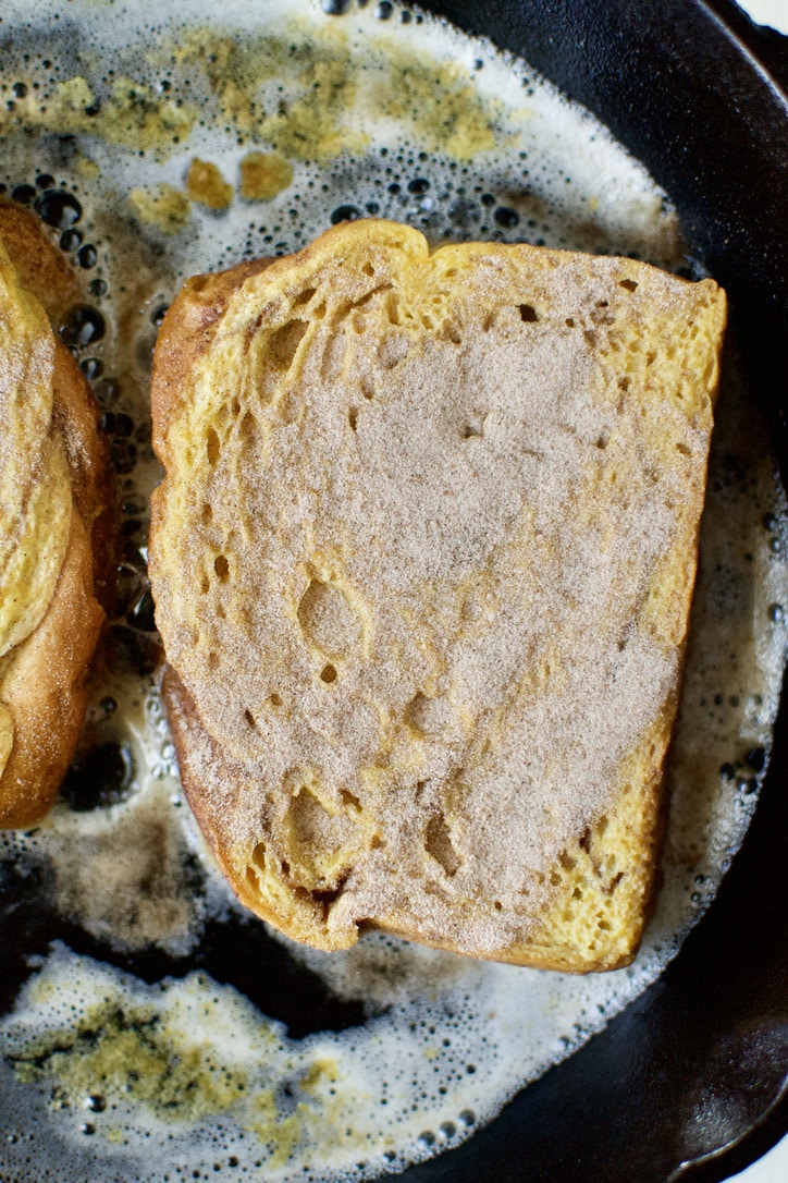 Cooking french toast with cinnamon sugar coating one side.
