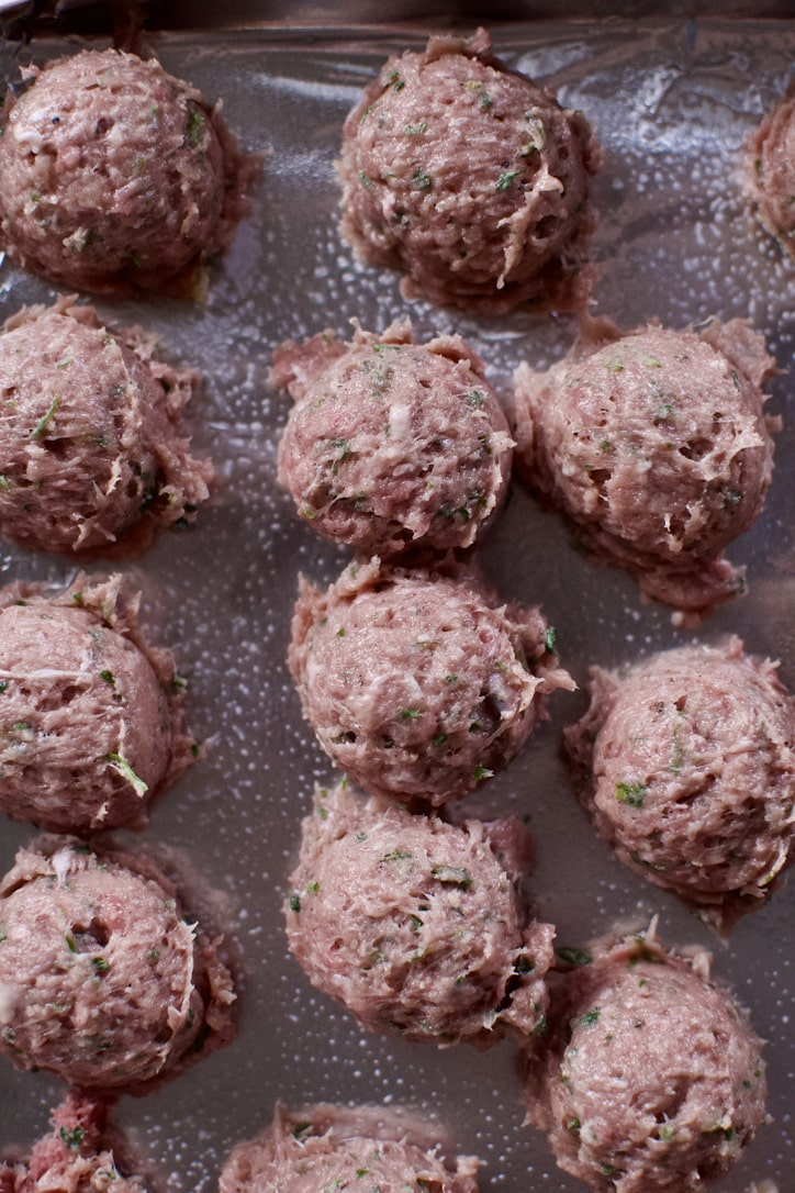 Meatballs scooped onto a tray, before final shaping.