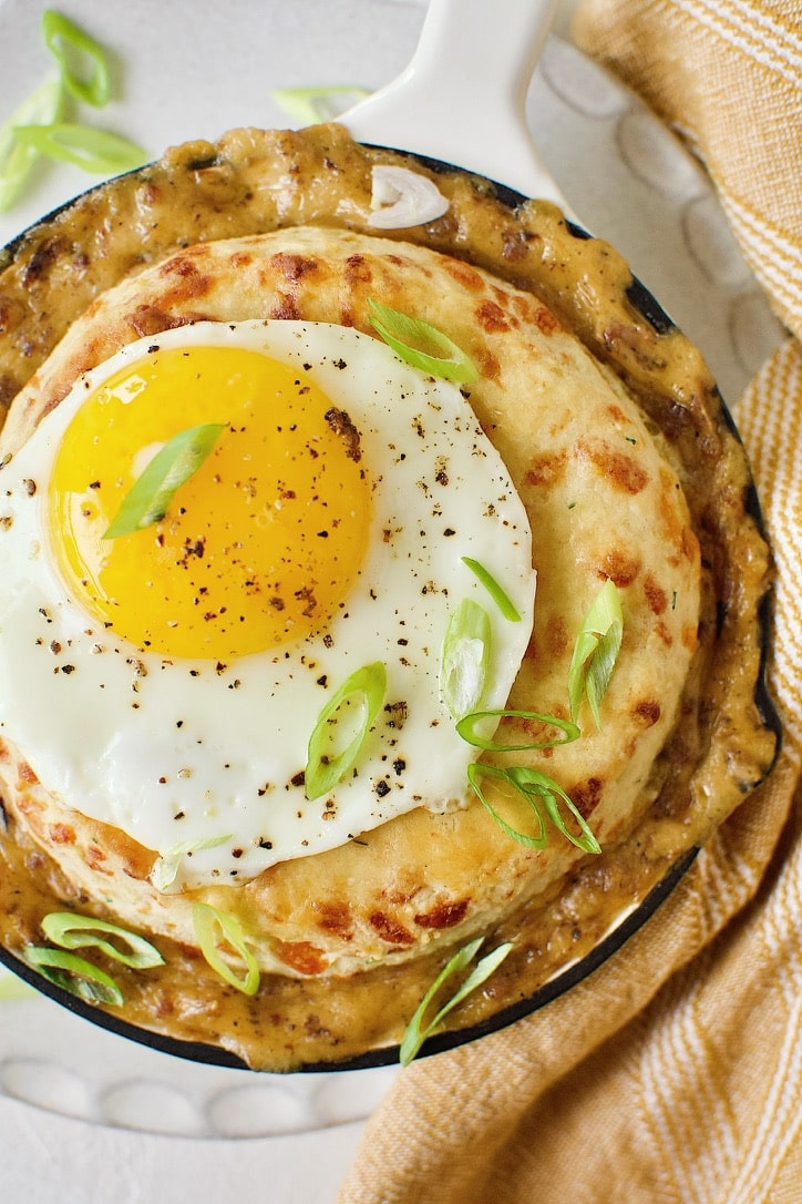 Breakfast Pie ready to eat. Topped with a fried egg and green onions.