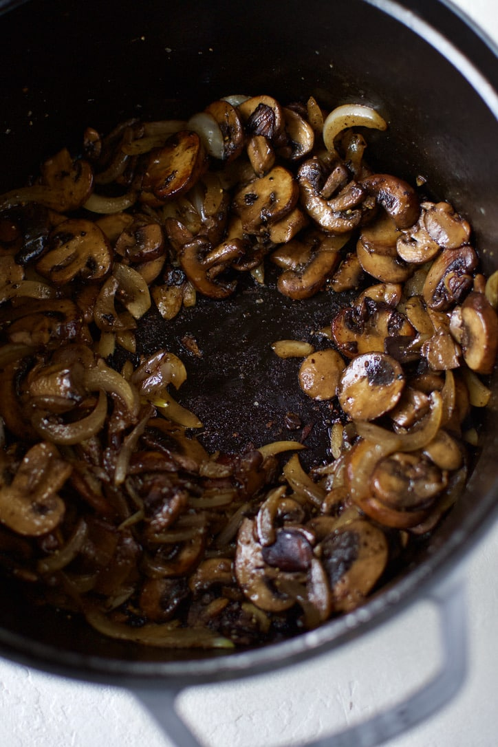 Mushrooms and Onions sweat in the bottom of a large pot.