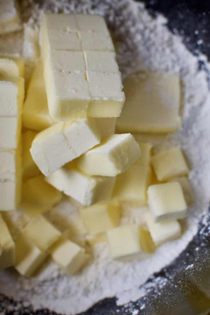 Adding the butter to the dry ingredients in the bowl of a stand mixer to make biscuit dough.